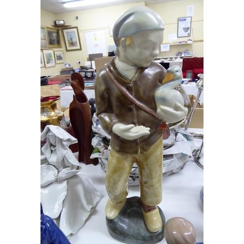 23 - A Dutch pottery figure on a boy holding a duck - ht 13 ins....