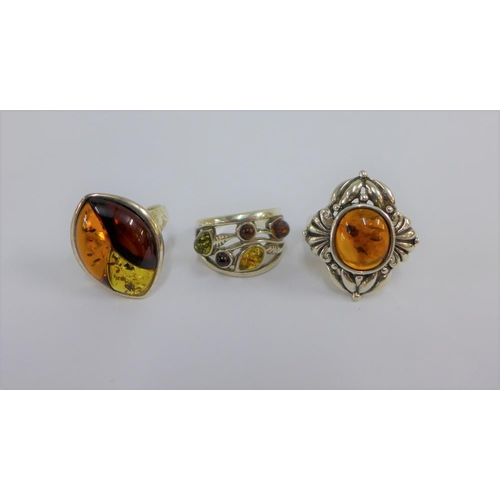 23 - Three silver and amber dress rings (3)...