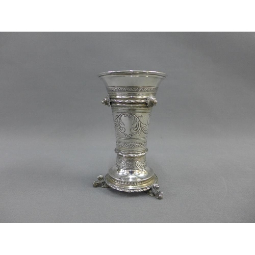25 - Eastern white metal vase, with flared rim, lion mask heads and engraved pattern, on a circular footr...