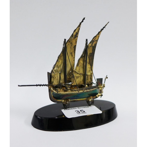 35 - Silver sailing boat dhow, stamped 925, on an ebonised oval stand, 9cm high...
