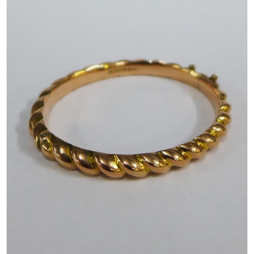 51 - Victorian 9ct gold bangle, with gadrooned pattern and hinged clasp, original black leather case...