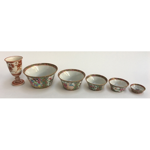 47 - A graduating set of famille verte bowls together with a small oriental cup with red underglaze, a bo...