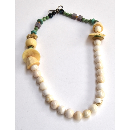 23 - Unusual necklace from Clouds, Woodstock, USA featuring various beads including a Nesuke rabbit and a...