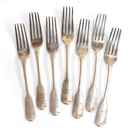 17 - A set of seven George IV silver fiddle pattern table forks, crested, by William Eley & William Fearn...