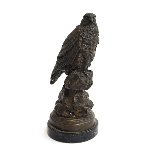 2 - A bronze sculpture of a seated peregrine falcon, raised on a plinth, 30cmH...