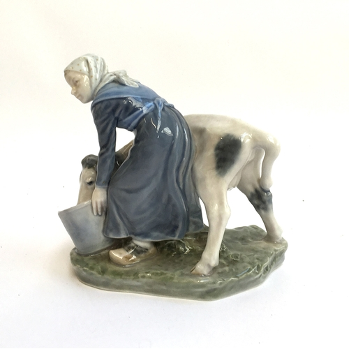 22 - A Royal Copenhagen figure group of a milkmaid and calf, model 779, the maid offering the calf a drin...