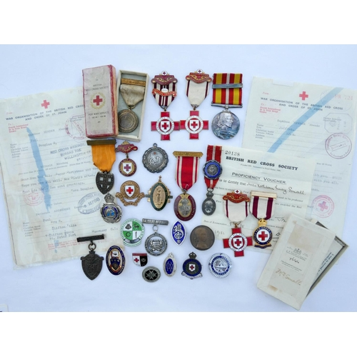 557 - A collection of Red Cross, St Johns Ambulance Brigade, Nursing and hospital medals, badges and insig...