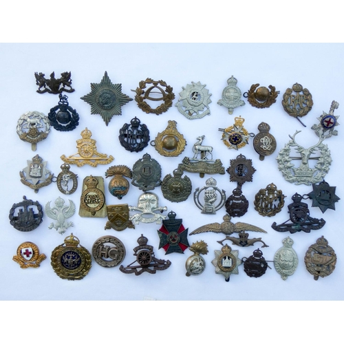 559 - A collection of approximately forty five British cap badges and insignia to include the Tank Corp, D...