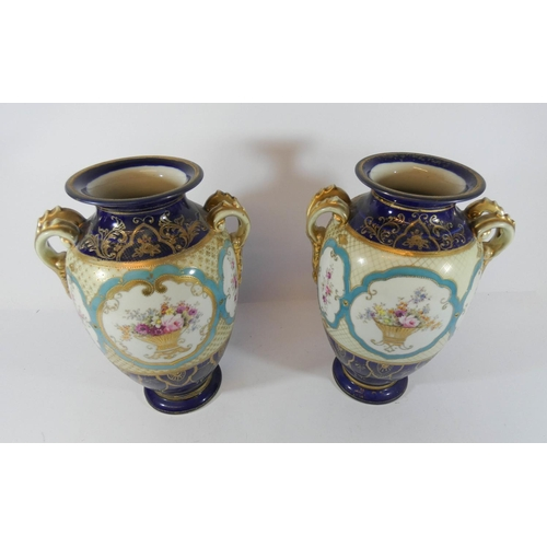 535 - A pair of Noritake twin-handled urn shaped vases, hand painted with flowers, 26 cms tall....