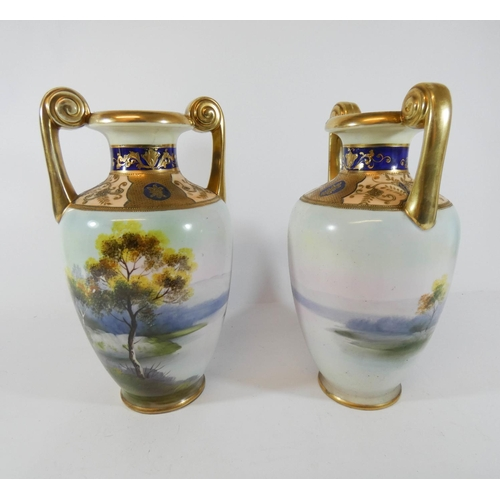 536 - A pair of Noritake twin-handled vases, hand painted with landscapes scenes. Height 25 cms...