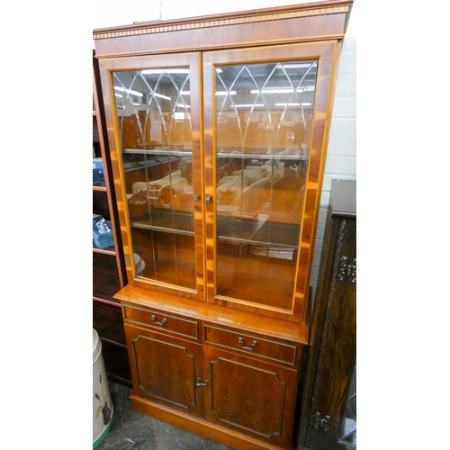 31 - A yew wood glazed bookcase standing on a drawer and cupboard base 3' wide...
