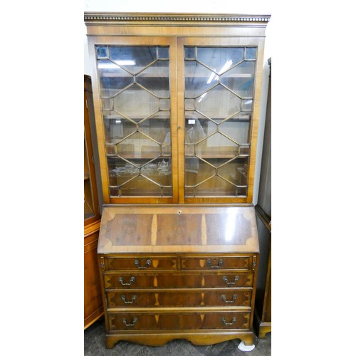 54 - A Georgian style yew wood lattice glazed bureau bookcase with three long and two short drawers under...