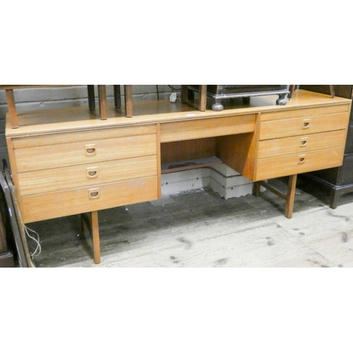 16 - A 1970's long low teak kneehole dressing table fitted seven drawers 6' wide...