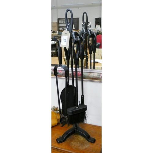 35 - A black iron four piece companion set...