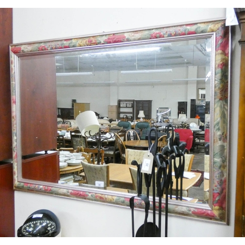 38 - A bevelled wall mirror in floral decorated frame...