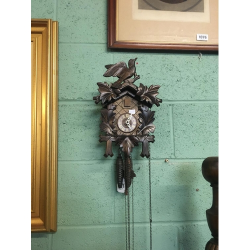 1077 - Black forest cuckoo clock with carved birds and leaves....