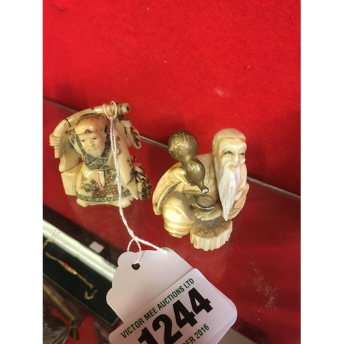1244 - Netsuke figure of man with oil bottle and man with shield....