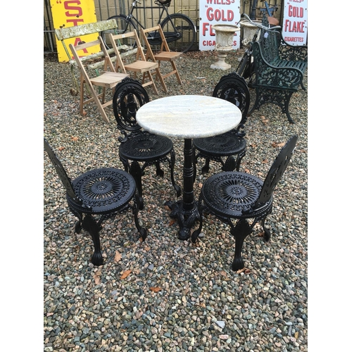 1349 - Garden set of four cast iron chairs and a cast iron marble topped table....