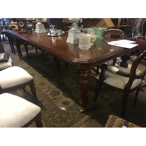 830 - Mahogany dining room table with reeded legs and brass castors. (280cm L x 113cm W)....