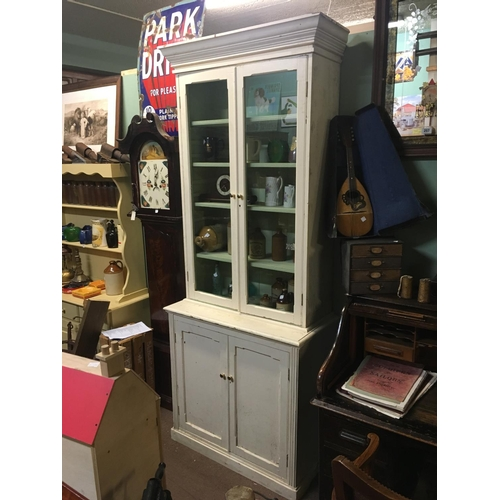 103 - Painted pine bookcase with two glazed doors over two panelled doors....