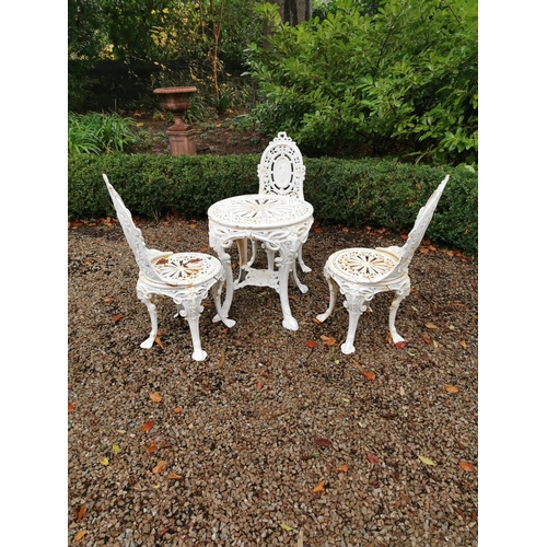 12 - Cast iron garden table and three matching chairs....