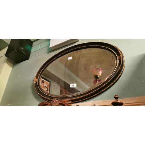 15 - 19th. C. ebonised and gilt oval mirror....