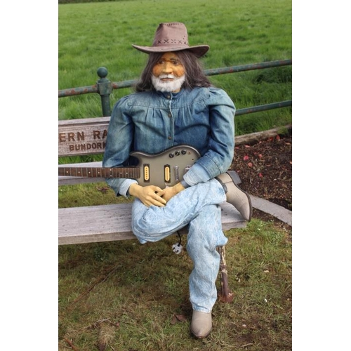 255 - Seated figure of Willie Nelson with guitar {182 cm H}....