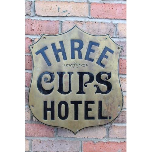 388 - Three Cups Hotel brass advertising shield {45 cm H x 40 cm W}....