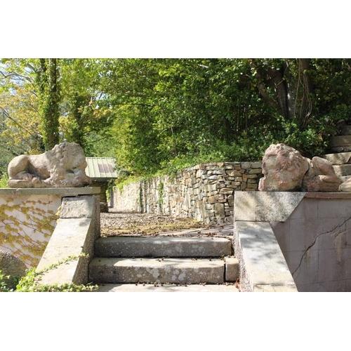 445 - Pair of cast stone models of seated Lions {45 cm H x 90 cm W x 30 cm D}....
