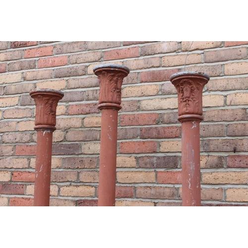 56 - Three decorative terracotta coloured aluminium Corinthian columns.{210 cm H x 20 cm Dia}....