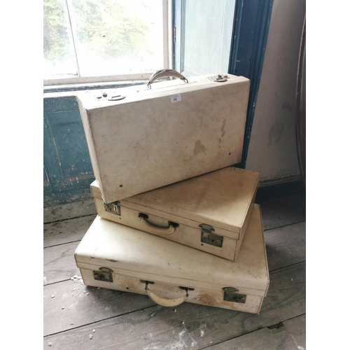 50 - Three white leather suitcases....
