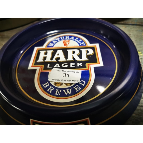 31 - Two Harp tinplate ashtrays....