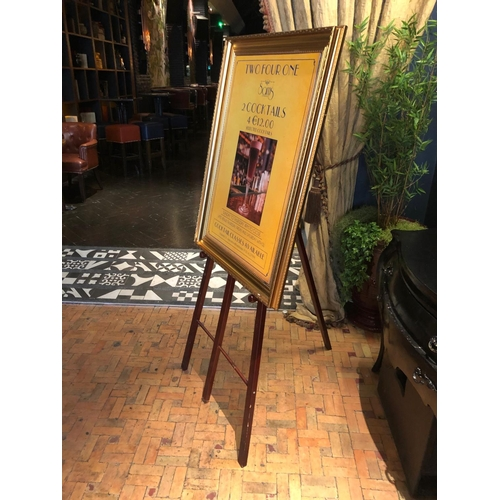 48 - Easel complete with gold framed advertisement W 75cm H 150cm...