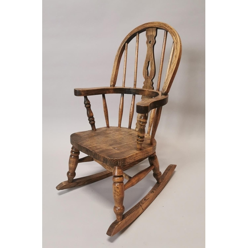 12 - Elm Windsor child's rocking chair. { 72cm H X 44cm W }....