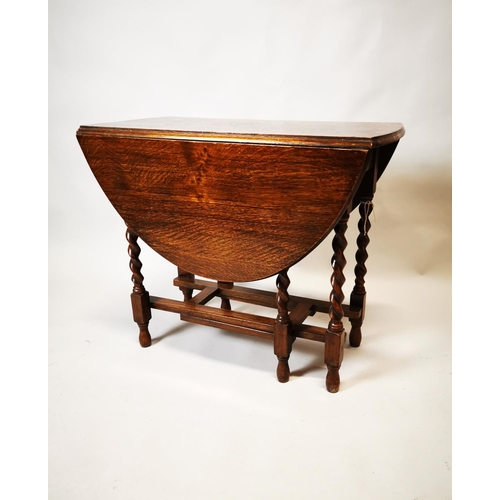 23 - Edwardian oak drop leaf table on barley twist legs. {72 cm H x 88 cm L x 46 cm D}...