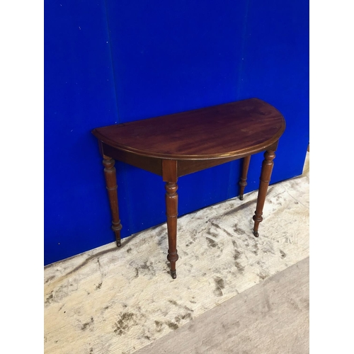 56 - Half moon shaped mahogany hall table on tapering turn legs W 108 H 73 D 50...