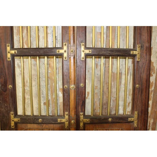 43 - Pair of oak doors with brass mounts and grille. {Each 256 cm H x 64 cm W}....