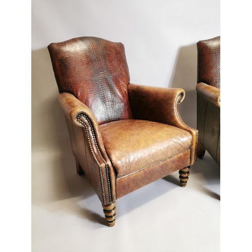 59 - Pair of leather upholstered armchairs raised on turned legs { 94cm H X 75cm W X 84cm D }.
