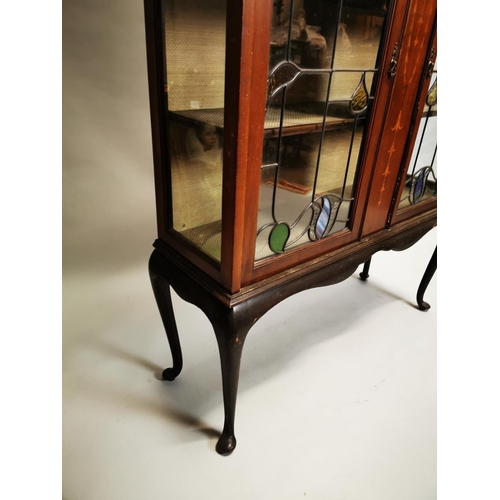 21 - Edwardian inlaid mahogany display cabinet the two glazed doors with coloured leaded glass inserts, r...