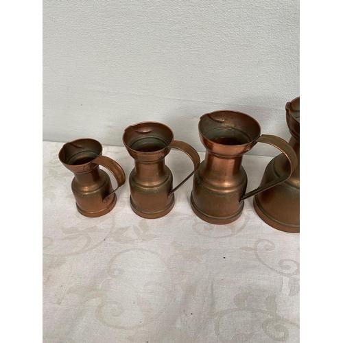 50A - Graduated set of five copper jugs