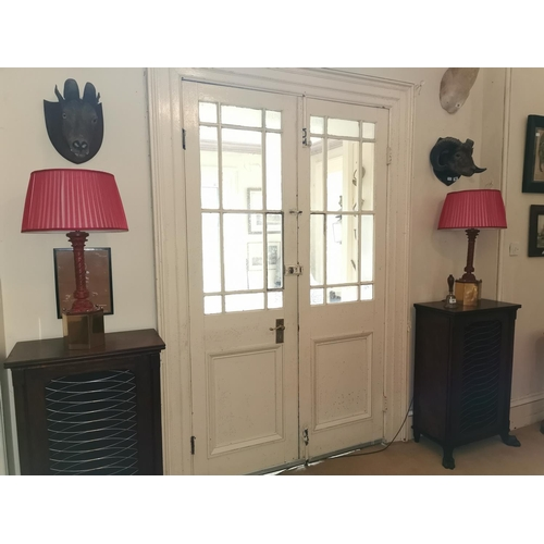 48 - Pair of decorative table lamps with octagonal brass base carved painted columns and red cloth shades...