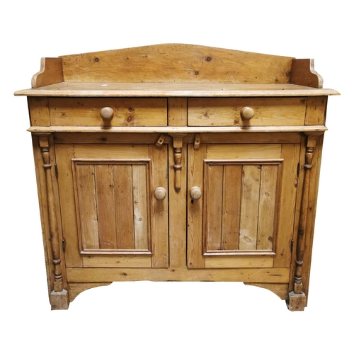 2 - 19th C. Irish Pine cabinet. The shaped gallery back above two short drawers over two panel doors fla...
