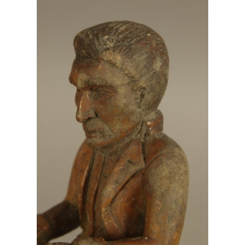 44 - FOLK ART, A CARVED WOODEN GENTLEMAN'S WALKING STICK, the terminal as a man seated on the head of a d...