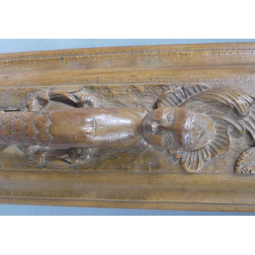42 - An oak door handle the long rectangular back plate carved in relief with flowers and leaf and curls ...