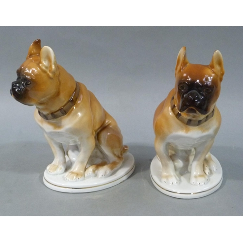 15 - A pair of Russian ceramic models of seated boxer dogs each on an oval plinth base with gilt rim line...