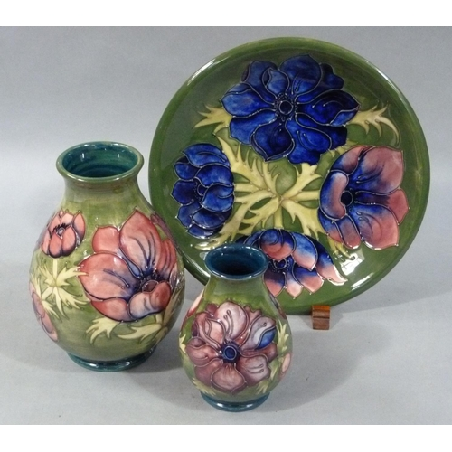 4 - Two Moorcroft Green Anemone vases of ovoid shape, 20cm and 14cm, together with a circular wall plate...