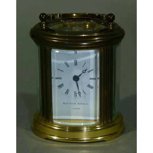 27 - A brass cased oval carriage time piece with swing handle, the white enamel face inscribed Matthew No...