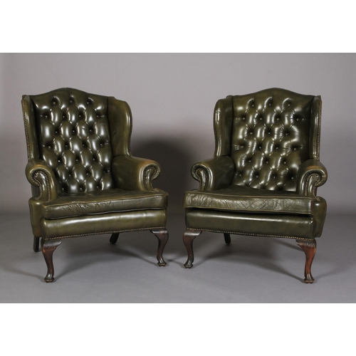 8 - A pair of button back green leather winged armchairs, with close nail studding, on cabriole legs wit...