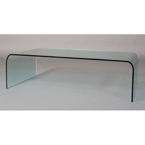 17 - A curved glass coffee table 130cm long x 69cm wide x 38cm high...