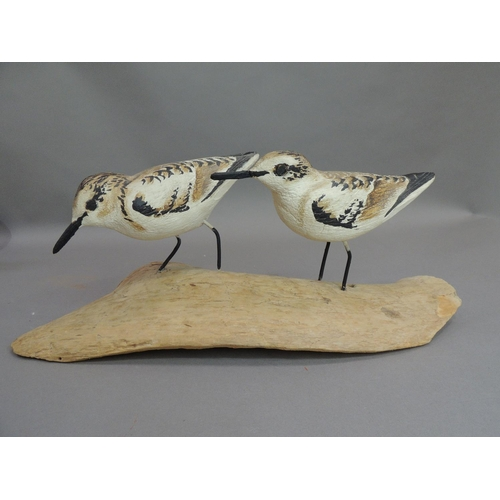 11 - Frank Shields - A pair of carved wooden birds on free form trunk, the base signed, 38cm wide